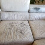 Close-up photo of scratches, body oil damage on white leather couch