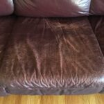 Close-up photo of wear on leather couch cushion