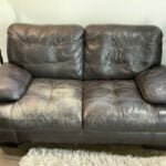 Picture of worn, discolored dark brown leather loveseat