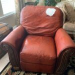 Picture of faded burgundy leather chair with large hole