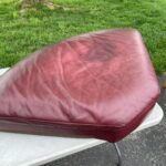 Picture of stains and fading on red leather couch cushion