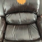Dark brown leather recliner with bright orange head spot discoloration